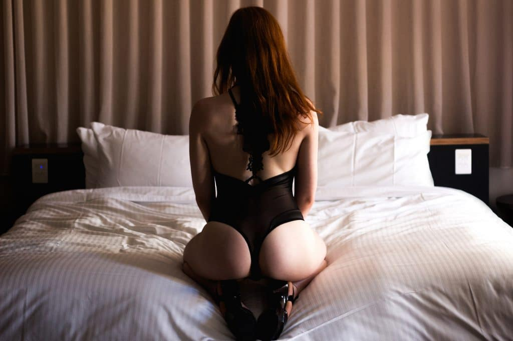 Sexy red head sat on bed