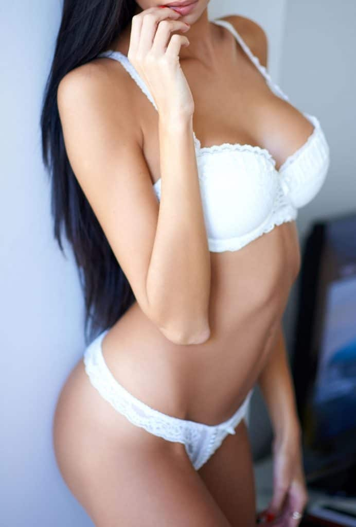 woman in white bra standing facing camera long black hair busty tanned beautiful naked
