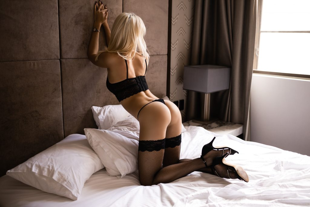 Giselle kneeling on bed sexual lingerie blonde